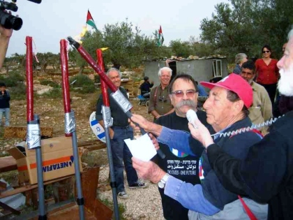 """For human dignity!"" - Yoshua Rosin of Gush Shalom lights a candle. Next to him: Teddy Katz, who constructed the Hanukkia"